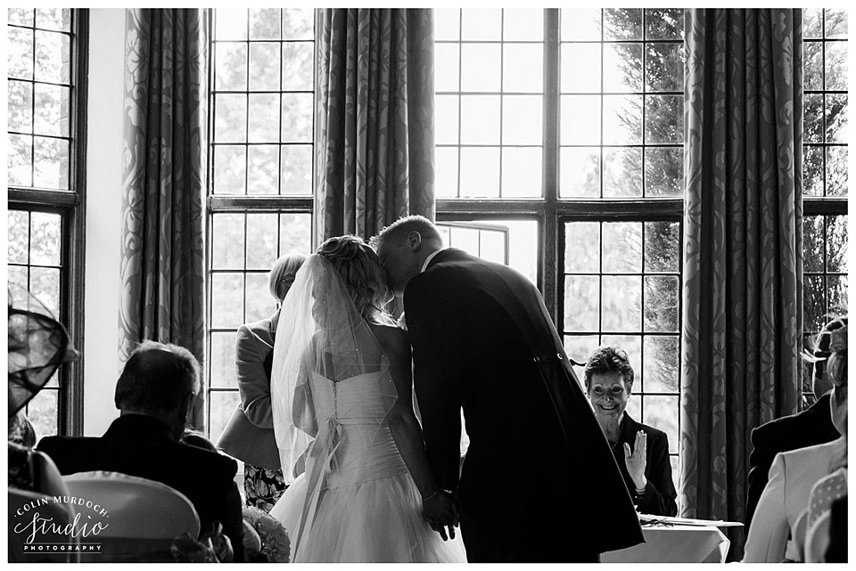 Bride and groom first kiss at a wedding at Aldwark Manor in Yorkshire