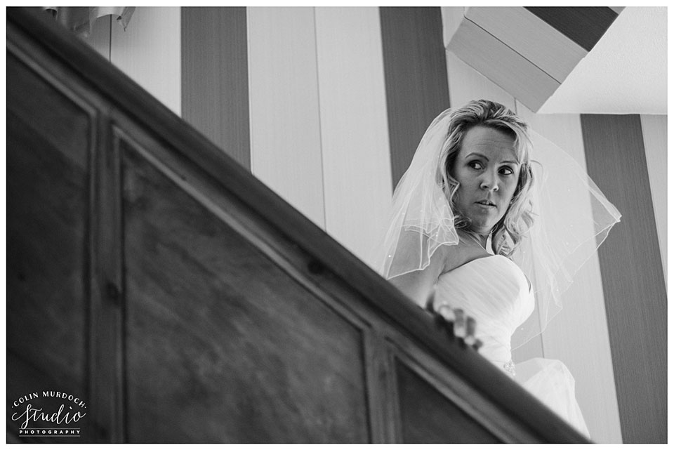 Bride walking down the stairs at Aldwark Manor