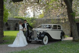 Newlyweds posing with a wedding car in Yorkshire